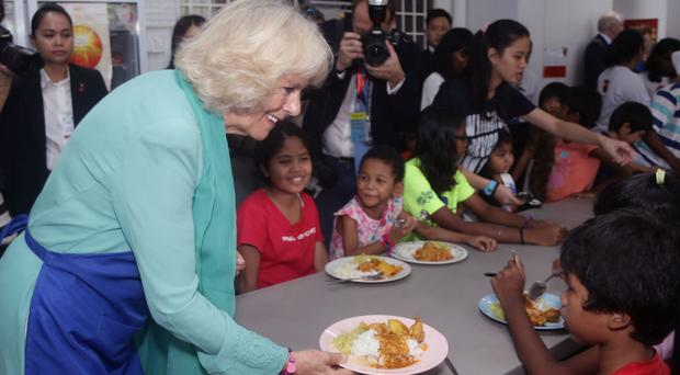 Camilla serves food for residents at The Lighthouse Children's Welfare Centre in Malaysia (Yui Mok/PA)