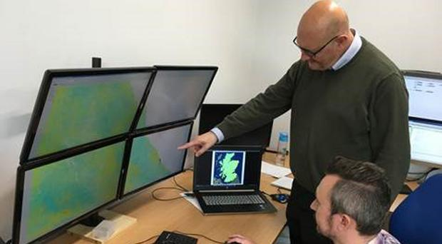 Dr Stephen Grebby of the University of Nottingham, seated, and Dr Andy Sowter of Geomatic Ventures Limited discussing the relative land motion map of Scotland (University of Nottingham/PA)
