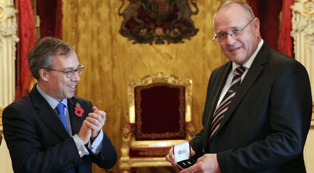 Lord Ed Llewellyn, left, awards Chris Norman the Queen's Commendation for Bravery, in Paris (Christophe Ena/AP)