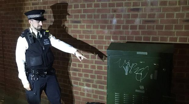 Inspector Aaron Clarke pointing at a British Telecom box