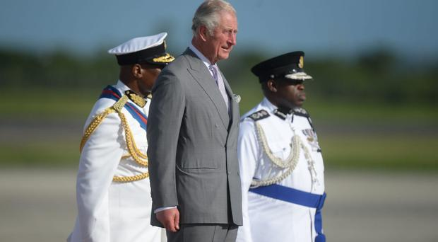 The Prince of Wales views a guard of honour as he arrives at VC Bird International Airport in Antigua (Victoria Jones/PA)