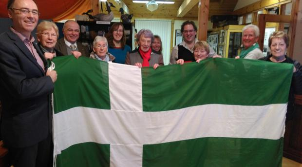 Alasdair Allan MSP, left, with the Barra Flag being held by Barra community members in Castlebay (Alasdair Allan/PA )