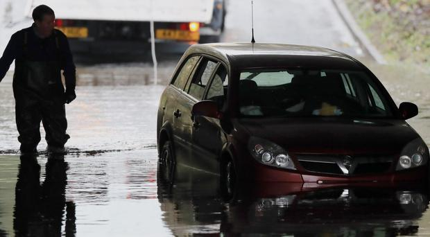 A car stuck in flood water under a bridge in Galgate, Lancashire (Peter Byrne/PA )