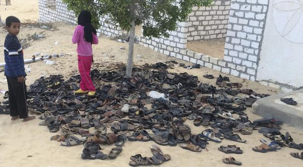 Discarded shoes of victims remain outside Al-Rawda Mosque in Bir al-Abd northern Sinai (AP)