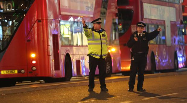 Police officers directing members of the public on Oxford Street in London after police responded to a number of reports of shots being fired on Oxford Street (Isabel Infantes/PA)