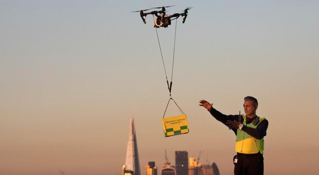 A drone delivery is collected demonstrating the carrying of medical supplies (David Parry/PA)