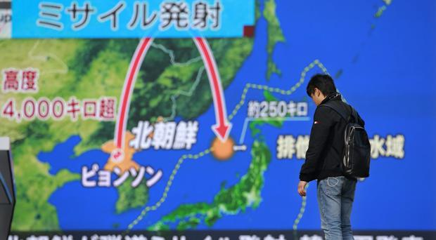 A man stands in front of a huge screen showing TV news programme reporting North Korea's missile launch, in Tokyo (Shizuo Kambayashi/AP)