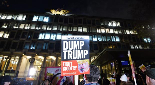 People take part in a protest against Donald Trump outside the US Embassy in London