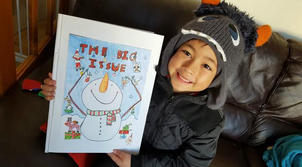 Martin Wellstead, aged six, with his winning design for the Christmas front cover of the Big Issue magazine (The Big Issue/PA)
