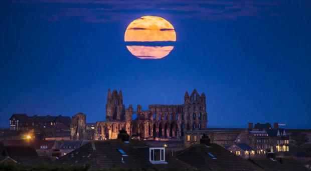 The Supermoon rises above Whitby Abbey in Yorkshire (Danny Lawson/PA)