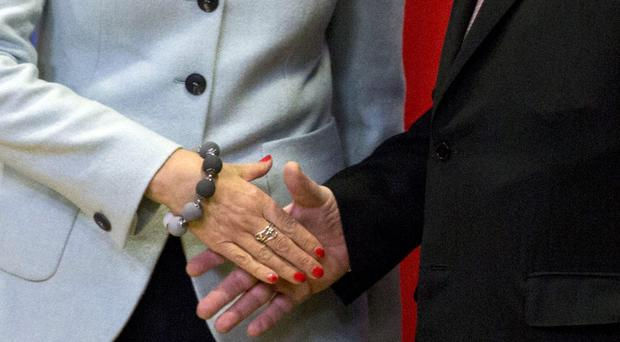 Theresa May shakes hands with European Commission President Jean-Claude Juncker (Virginia Mayo/AP)