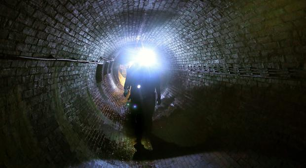 An engineer walks through a Victorian built sewer system (Gareth Fuller/PA)