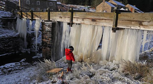 Three-year-old Reuben looks at a wall of icicles at Killhope mine in County Durham (Owen Humphreys/PA)