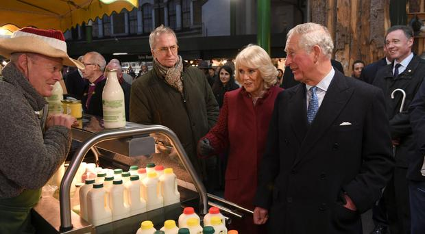 Charles and Camilla meet stall-holders and members of the local community in Borough Market (Clodagh Kilcoyne/PA)