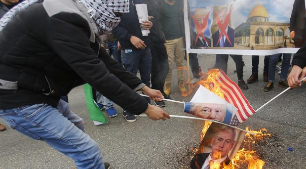 Protesters burn images of US President Donald Trump and sraeli Prime Minister Benjamin Netanyahu in the West Bank city of Ramallah (Nasser Shiyoukhi/AP)