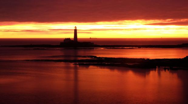 The sun rises behind St Mary's lighthouse in Whitley Bay (Owen Humphreys/PA)