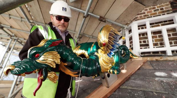 A workman holds one of the dragons that are being replaced on the 163ft tall Great Pagoda in the Royal Botanic Gardens (Steve Parsons/PA)