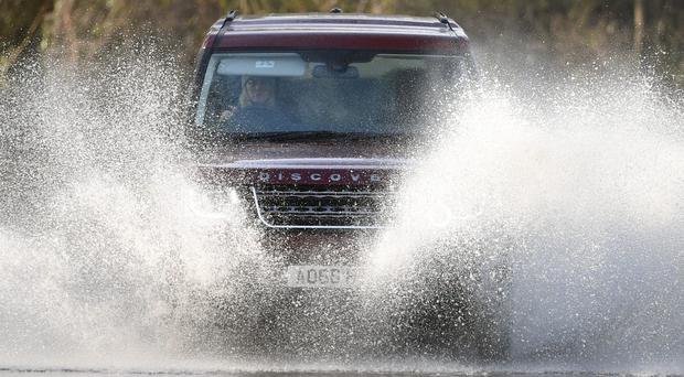 Cars make their way through flood water near Chediston in Suffolk (Joe Giddens/PA)