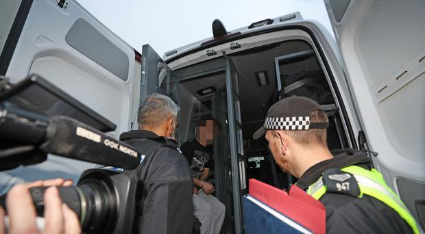 Police lead away a man after a raid at an address in Stockton, Teesside, as part of a crackdown on people trafficking and serious sexual offences. (Owen Humphreys/PA)