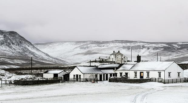 A farm house blanketed by snow near Langdon Beck, as dawn breaks in the North Pennines