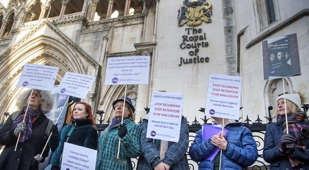 Women take part in a demonstration outside the High Court in London before a case brought by former sex workers against the government (Victoria Jones/PA)