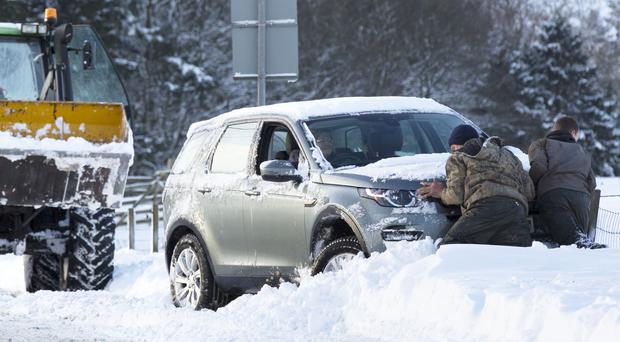 Drivers help to push a vehicle back on the road after heavy snow (David Cheskin/PA)