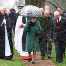 Queen Elizabeth II and the Duke of Edinburgh (second right) leave after attending a church service at St Lawrence Church, Norfolk