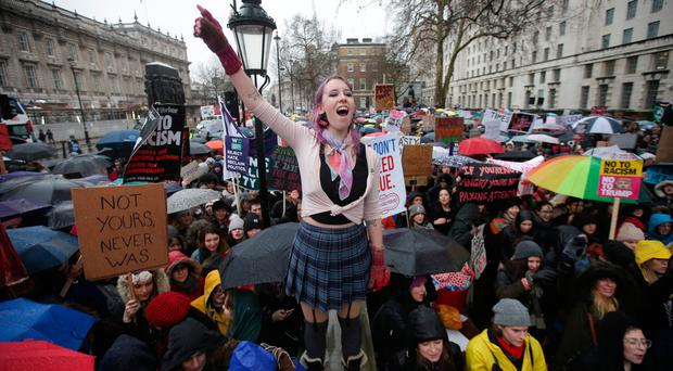 Protesters hold up placards during the Women's March in London