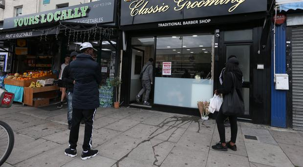 Floral tributes laid outside shops in Kingsland Road, east London where Rashan Charles died (Jonathan Brady/PA)