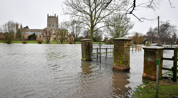 Standing water covers the park and road behind Tewkesbury Abbey (Ben Birchall/PA)