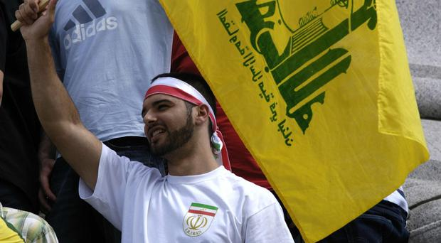 A protester flies a Hezbollah flag in Trafalgar Square in London (Andrew Stuart/PA)
