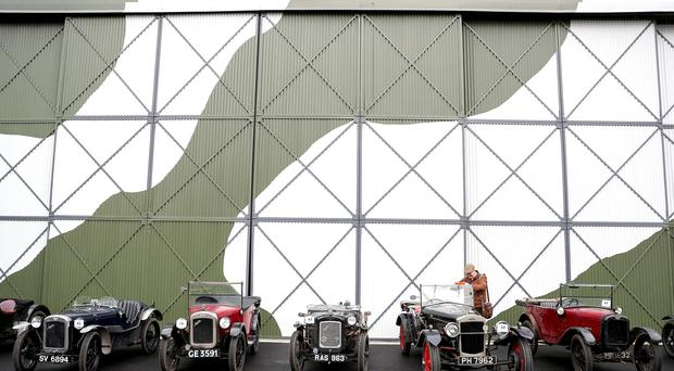 A man takes a photo of a line-up of pre-war MG cars during the annual driving tests for the Vintage Sports-Car Club, around courses laid out at the Brooklands Museum site, in Weybridge, Surrey