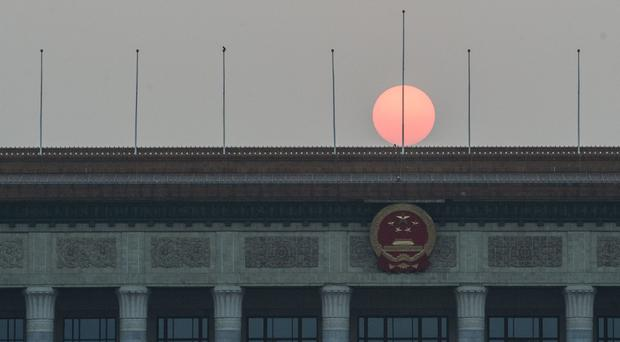 The sun sets over the Great Hall of the People on Tiananmen Square in Beijing (Stefan Rousseau/PA)
