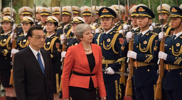 Theresa May warns China to play by worldwide  rules