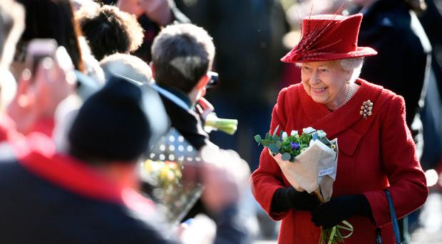 The Queen greets well-wishers as she attends St Peter and Paul Church in West Newton, Norfolk