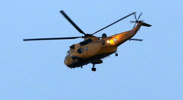 A rescue helicopter over the Cairngorms where two skiers have gone missing in the Highlands