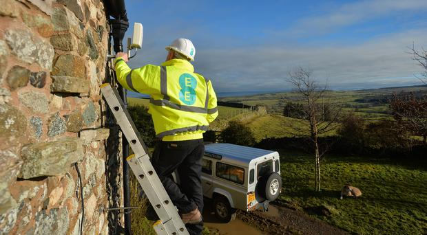 An EE engineer installs a 4G antenna to a home in the Cumbrian North Fells (Mark Runnacles/PA)