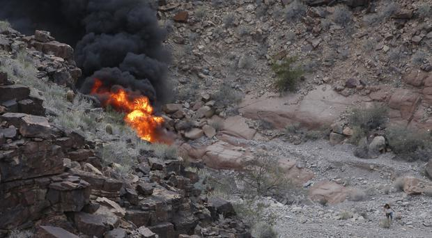 A woman walks away from the burning wreckage of the helicopter which crashed in the Gran Canyon (Teddy Fujimoto/AP)