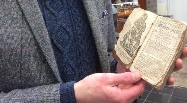 Jim Spencer, of Hansons Auctioneers, with the book dating to 1720