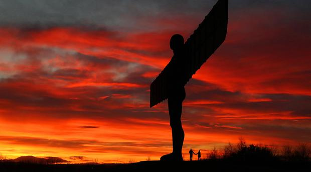 The sun setting behind the Angel of the North (Owen Humphreys/PA)