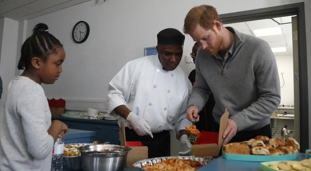 Prince Harry serves pasta during a visit to Roundwood Youth Centre in Brent,(Frank Augstein/PA