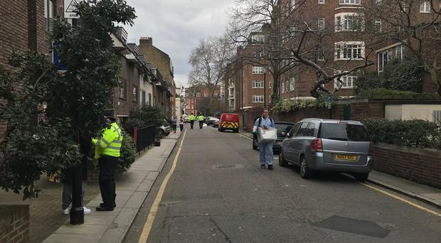 Police and forensic officers in Logan Place, Kensington (Ryan Hooper/PA)
