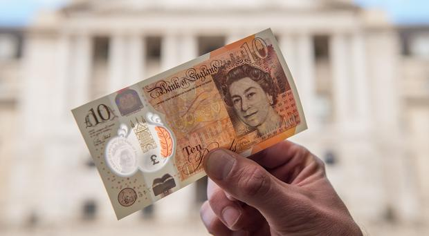 A man holds a new ten pound note featuring Jane Austen outside the Bank of England in London (PA Wire / Dominic Lipinski)