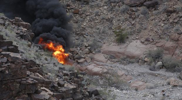 A survivor, lower right, walks away from the scene of the helicopter crash along the jagged rocks of the Grand Canyon, in Arizona