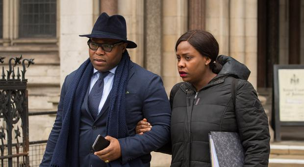 Isaiah Haastrup's father Lanre Haastrup and mother Takesha Thomas leave the Royal Courts of Justice, London (Dominic Lipinski/PA)