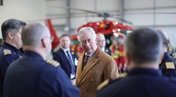 The Prince of Wales speaks to pilots and engineers during a visit to the South Wales airbase of the Wales Air Ambulance Charity in Dafen, South Wales (Aaron Chown/PA)