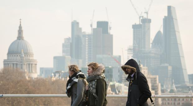 People in winter coats and scarves cross Waterloo Bridge (Dominic Lipinski/PA)