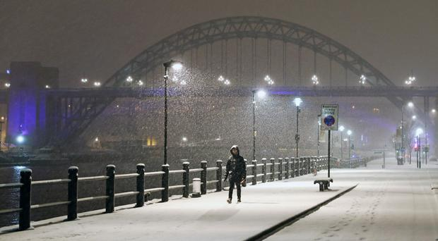 A person walks through Newcastle Quayside following heavy overnight snowfall (Owen Humphreys/PA)