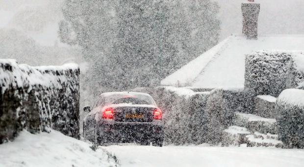A car travels through snow in Ashford, Kent (Gareth Fuller/PA)