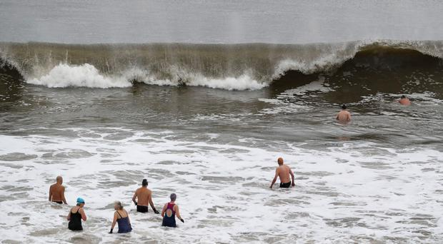 Brave swimmers enter the North Sea for a dip as giant waves lash the shore (Owen Humphreys/PA)